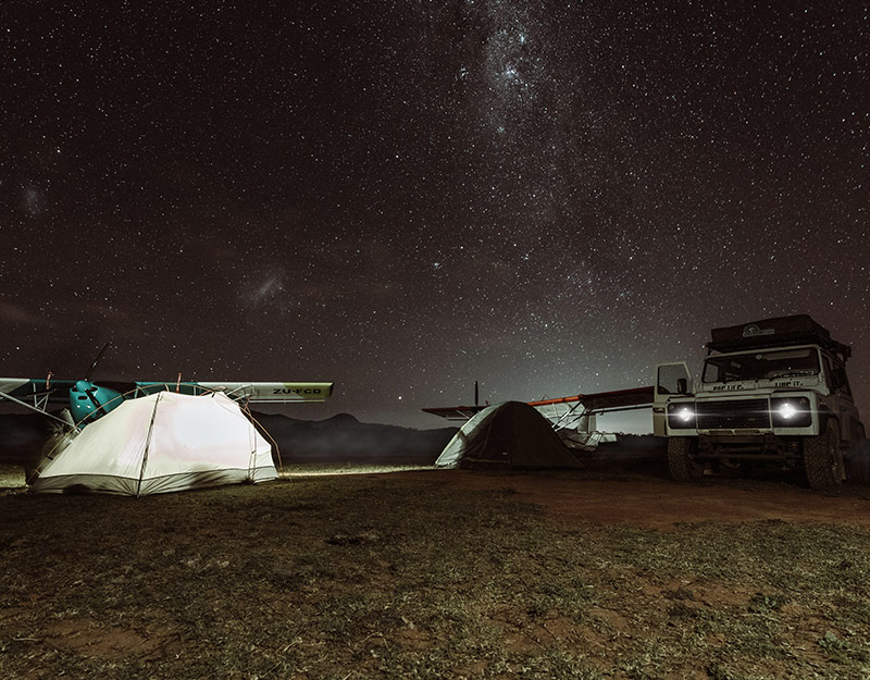 Campfire with stars and Land Rover in South Africa